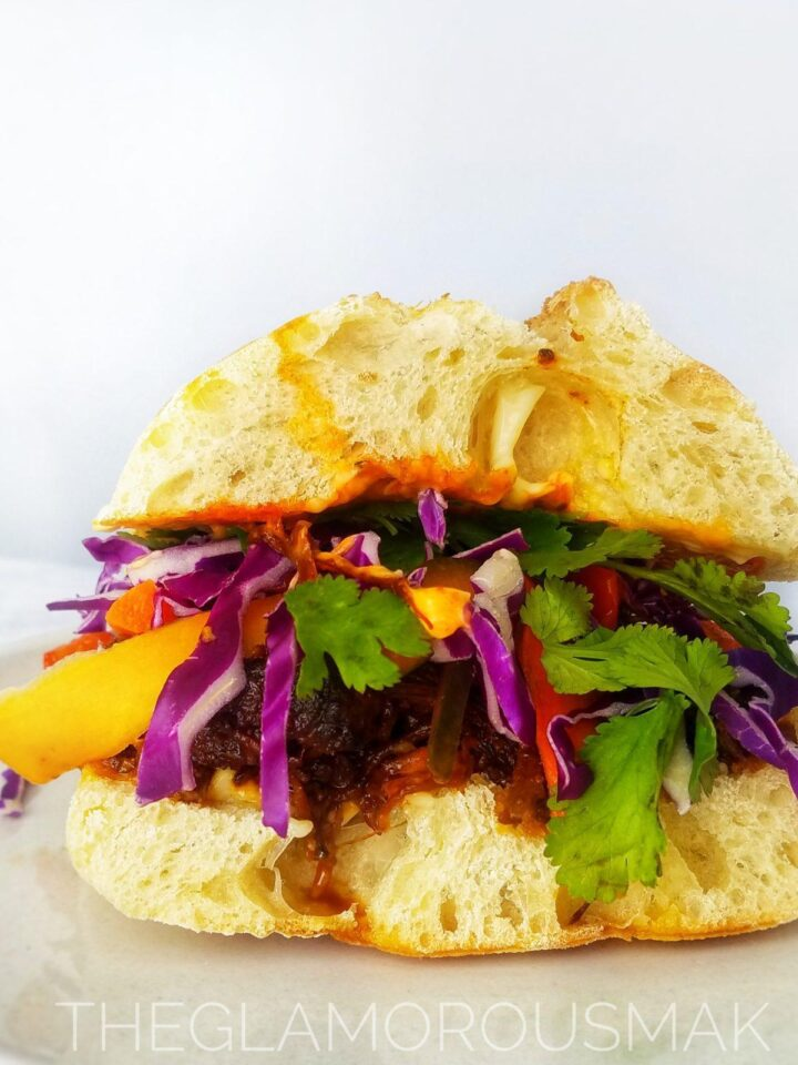 banh mi sandwich with pickled vegetables, cilantro and red cabbage. These easy banh mi pulled pork sandwich recipe is vietnamese street food made right in your crockpot slow cooker. topped with quick pickled vegetables perfect for meal planning, meal prep, lunch, dinner, meal ideas. Easy marinade, healthy.