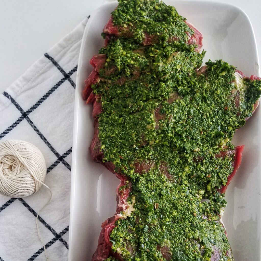 mandyolive.com boneless leg of lamb recipe topped with pesto.