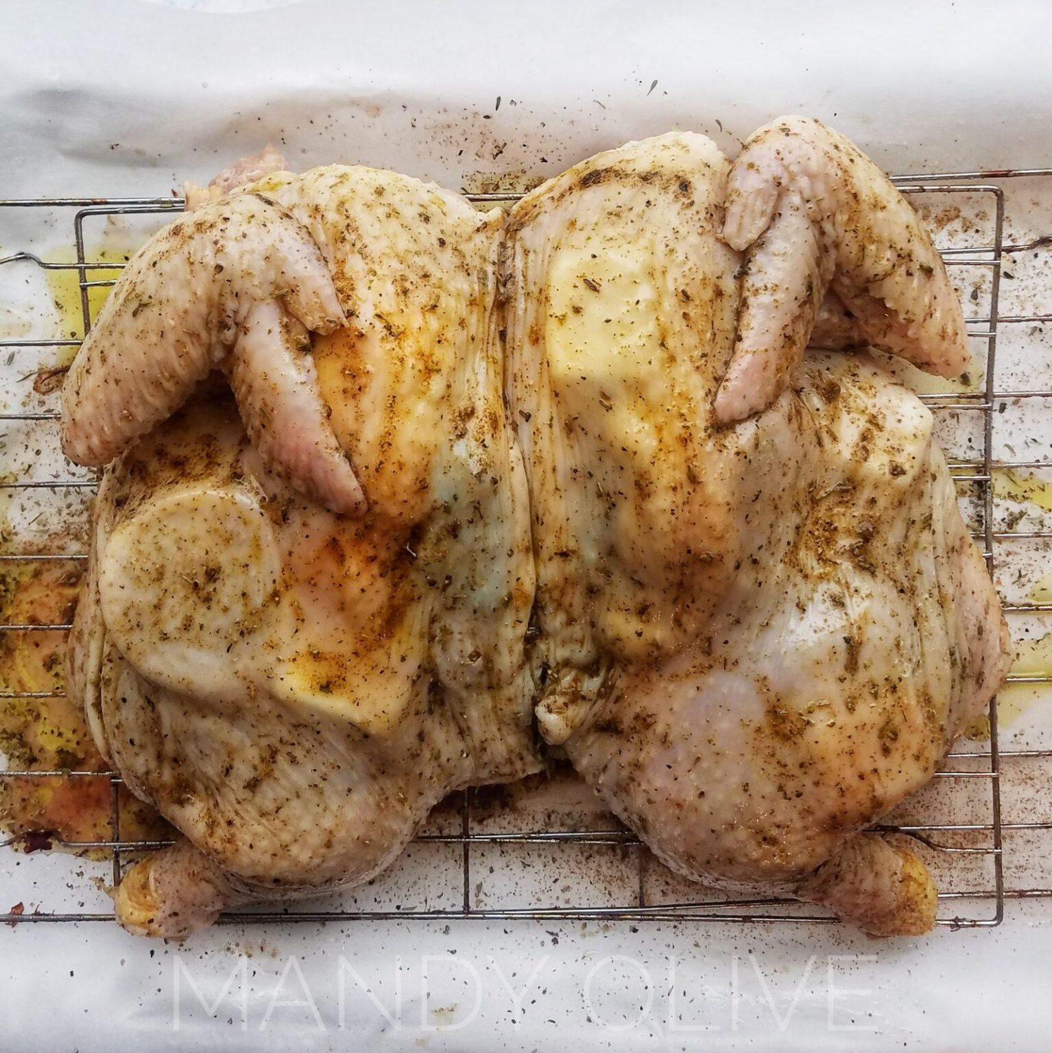 This picture shows a spatchcock chicken stuffed with lemon and butter. This spatchcock chicken recipe is a quick, simple and easy way to make moist juicy chicken with crispy chicken skin. How to roast a whole chicken in the oven on a sheet pan for dinner, meal prep with butterflied chicken. What to do with a whole chicken? How to bake a whole chicken for dinner idea and meal prepping.