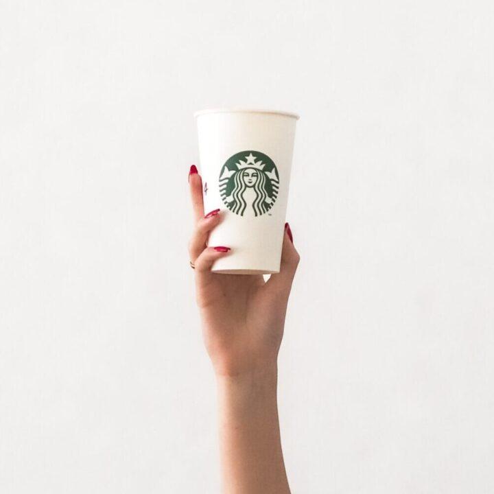 woman's arm holding a starbucks apple crisp macchiato. Starbucks copycat apple crisp macchiato recipe on mandyolive.com
